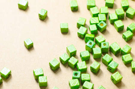 cubic: green wooden cubic beads on paper background Stock Photo