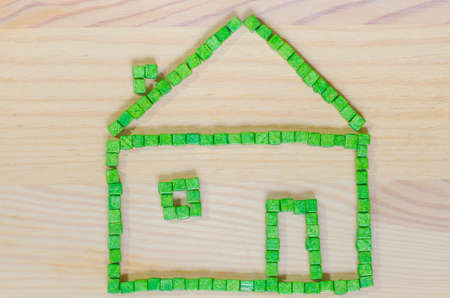 building color: green house made with   toy blocks on wooden background