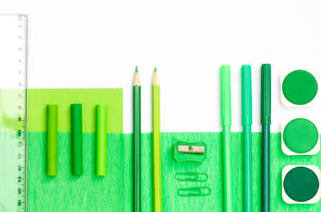 pedant: green color school supplies on white paper background