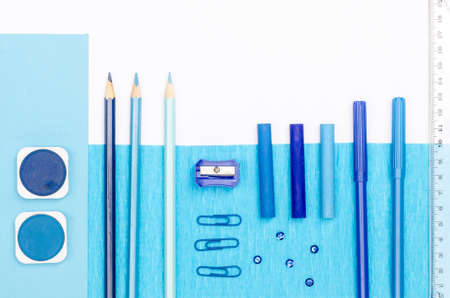 pedantic: blue color school supplies on white paper background