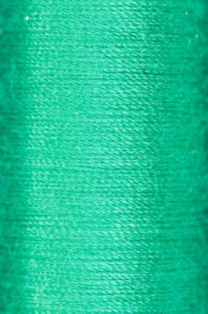 silk background: bobbin of green thread background texture macro