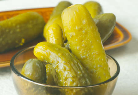 brine: pickled cucumbers in brine on table Stock Photo