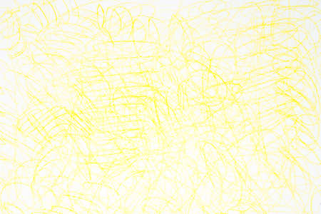 manually: yellow crayon doodles on white paper background