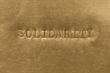 solidaridad: palabra solidaridad impreso en el fondo met�lico de oro