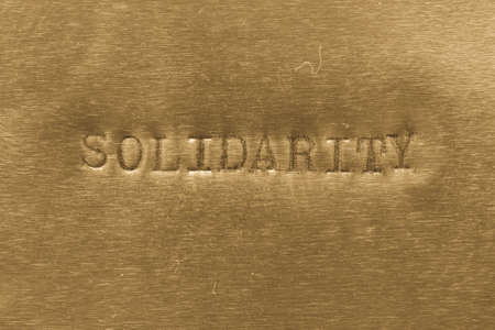 tightness: word solidarity printed on golden metallic background