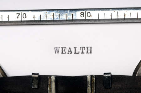 typed: word wealth typed on  old typewriter Stock Photo