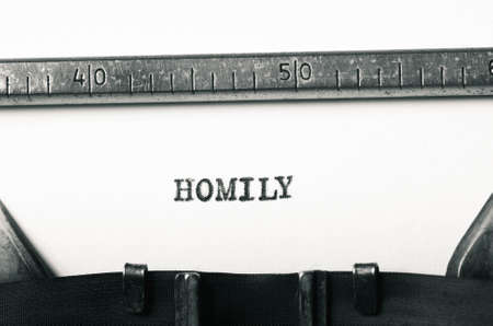 typed: word homily typed on old typewriter