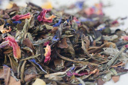 theine: closeup to dried white tea leaves with flower petals