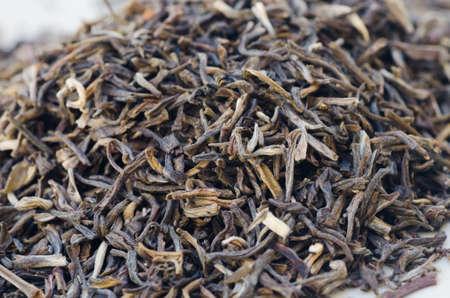 theine: closeup to dried green tea leaves