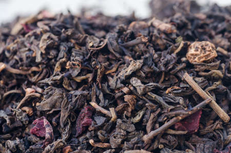 theine: closeup to dried black tea leaves and fruits Stock Photo