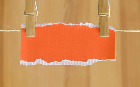 peg: blank orange piece of paper and clothes peg Stock Photo