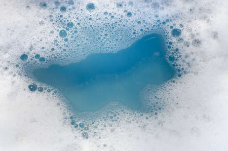 closeup to white foam on blue water Stock Photo
