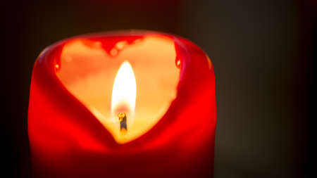 red heart shape burning candle in night