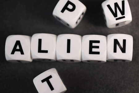 orthography: word alien on white toy cubes