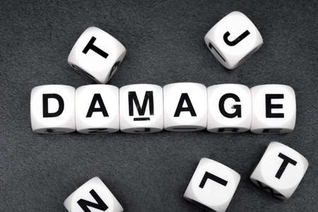 orthography: word damage on white toy cubes Stock Photo