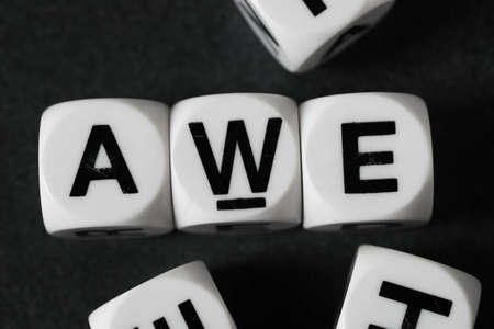 orthography: word awe on white toy cubes