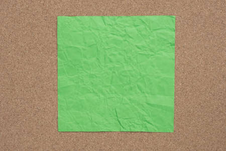 green color creased paper note on cork background