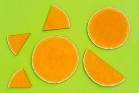 slices of pumpkin on green plastic cutting board top view Stock Photo