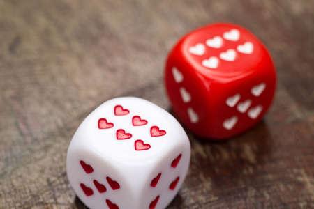twee dobbelstenen met harten op houten tafel