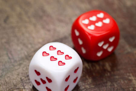 two dices with hearts on wooden table Stock Photo