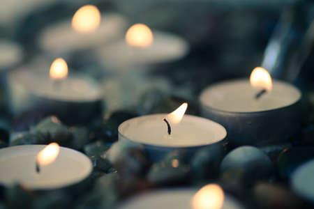 tea-light candles on pebbles stones selective focus closeup