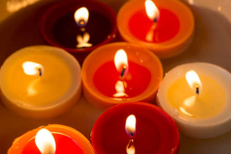 closeup to burning multicolored candles in darkness