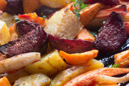 baked vegegetables roots macro: carrot, potato, beet, parsley Imagens