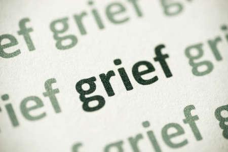 word grief printed on white paper macro