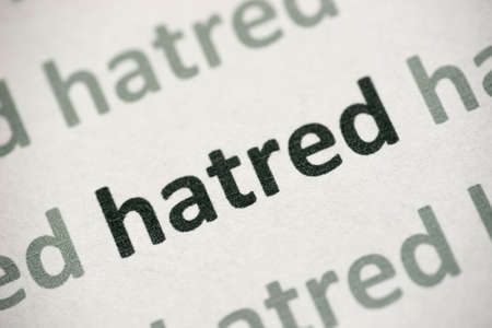 word hatred printed on white paper macro Archivio Fotografico - 105637076