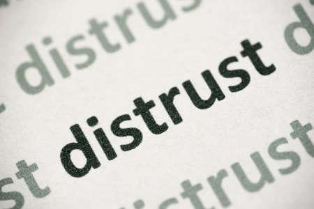 word distrust printed on white paper macro
