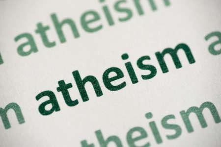 word atheism printed on white paper macro