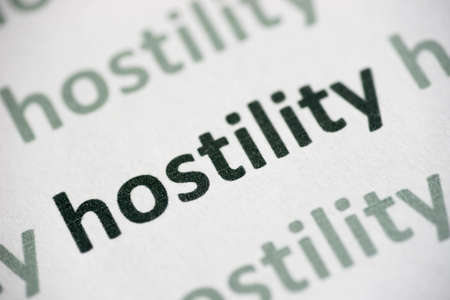 word hostility printed on white paper macro Stock Photo