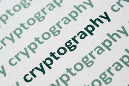 word cryptography printed on white paper macro Stock Photo