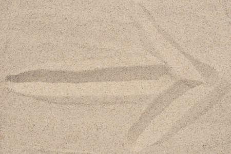 arrow sign on natural sand texture background closeup Imagens