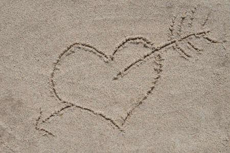 Dibujo de corazón y flecha sobre fondo de arena arena