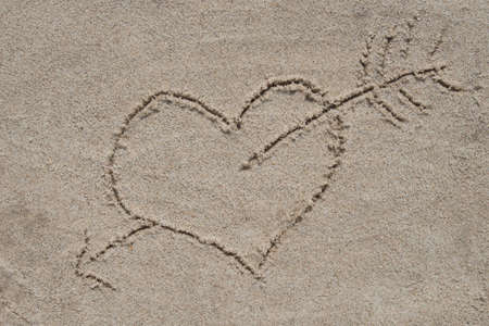 heart and arrow drawing on sand sand background