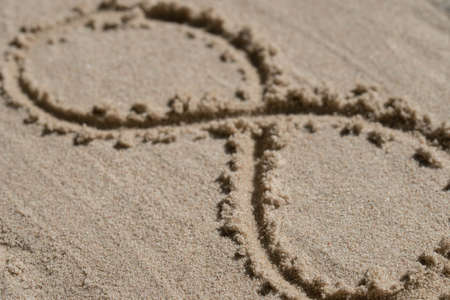 infinity symbol - drawing on sand background