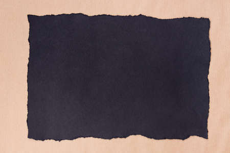 black color piece of torn paper on recycled paper background texture