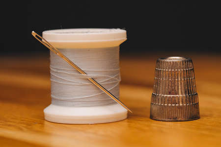 thimble and thread with needle on table. Stock Photo