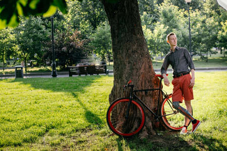 Hipster with red bycicle and tattoo on leg in park Stock Photo