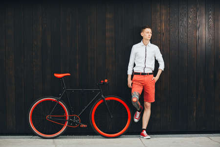 Hipster with bycicle and tatoo at dark background. 스톡 콘텐츠 - 92048474