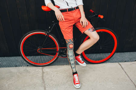 Hipster with bycicle and tatoo at dark background.