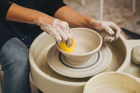 Potter at work. Creating dishes. Potters wheel. Dirty hands in the clay. Working potter. Stock Photo
