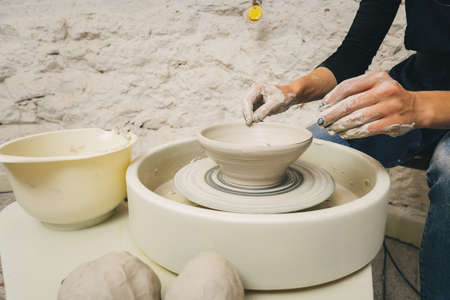 Potter at work. Creating dishes. Potter's wheel. Dirty hands in the clay. Working potter.