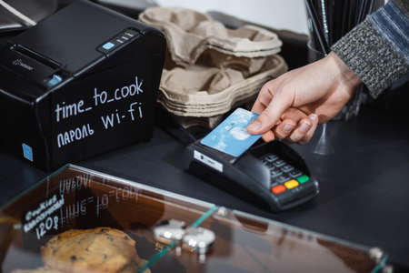 Customer is paying with contactless credit card in shop. 스톡 콘텐츠