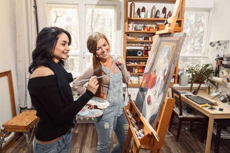 two girls in an artist studio. paints model