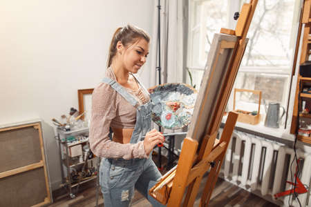 Smiling girl paints on canvas with oil colors in workshop 스톡 콘텐츠