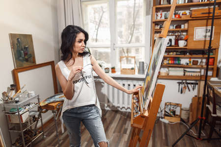 Smiling girl paints on canvas with oil colors in workshop Foto de archivo