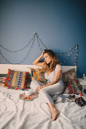 Young beautiful woman drink coffee at home lying on bed.