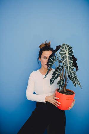 Portrait of beautiful fashion girl with plant on blue background Foto de archivo